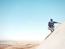 Mensenzitting op een klip en het bekijken de woestijn stock foto