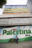 Mensenzitting op een stoel en het schilderen van Chavez en Viva Palestina Royalty-vrije Stock Fotografie
