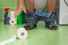 Mensenzitting op een toilet in een familiehuis Buik pijn diarree Royalty-vrije Stock Afbeelding