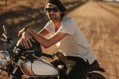Mensenzitting op een uitstekende motorfiets in openlucht stock afbeelding