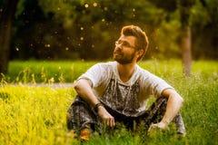 Mensenzitting op gras bij het park op mooie zonnige dag Royalty-vrije Stock Afbeeldingen
