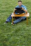 Mensenzitting op het gras buiten voor een lijst met een koeler stock foto's