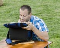 Mensenzitting op het gras buiten voor een lijst met een koeler royalty-vrije stock afbeelding