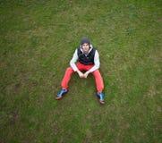Mensenzitting op het gras in de herfst met rode broek royalty-vrije stock fotografie