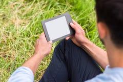 Mensenzitting op het groene gras met zijn rug en met apparaat stock fotografie