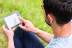 Mensenzitting op het groene gras met zijn rug en lezing op apparaat stock foto's