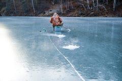 Mensenzitting op het ijs die naast hem barst op duidelijk ijs vissen royalty-vrije stock afbeeldingen