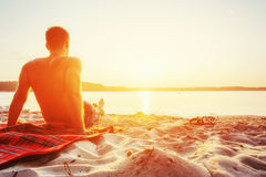 Mensenzitting op het zand bij zonsondergang Stock Foto