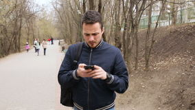Mensenzitting op parkbank met mobiele telefoon stock videobeelden