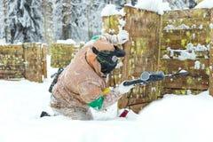 Mensenzitting op sneeuw achter het houten vestingwerk paintbal spelen Stock Fotografie