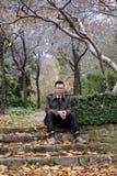 Mensenzitting op stappen bij een park in de dalingsseizoen/herfst Royalty-vrije Stock Afbeeldingen