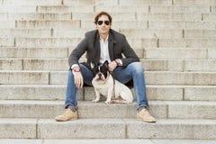 Mensenzitting op treden naast zijn hond royalty-vrije stock foto