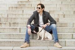 Mensenzitting op treden naast zijn hond royalty-vrije stock afbeeldingen
