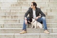 Mensenzitting op treden naast zijn hond royalty-vrije stock afbeelding