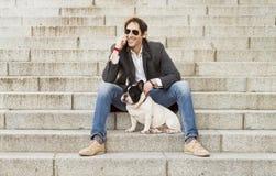 Mensenzitting op treden naast zijn hond en het spreken telefonisch stock afbeeldingen