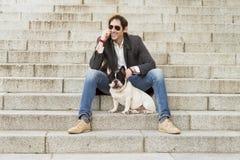 Mensenzitting op treden naast zijn hond en het spreken telefonisch stock foto
