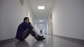 Mensenzitting op vloer van lange witte gang en het spreken op mobiele telefoon stock videobeelden
