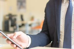 Mensenzitting terwijl het gebruiken van mobiele smartphone Zekere Ondernemer die aan telefoon werken royalty-vrije stock afbeelding