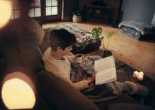 Mensenzitting thuis en lezingsboek stock afbeeldingen