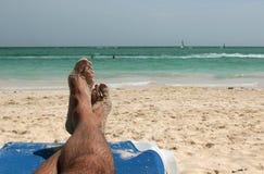 Mensfüße auf einem sandigen Strand Stockfotos