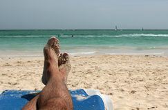 Mensfot på en sandig strand Arkivfoton