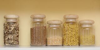 Mensola con i contenitori dei cereali Immagini Stock Libere da Diritti