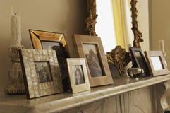 Mensola del camino di marmo del camino con le immagini e lo specchio incorniciati immagine stock libera da diritti