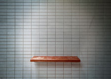 Mensola di legno sulla parete delle mattonelle. Fotografia Stock