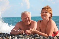 Mensonge âgé heureux de paires sur Pebble Beach Photographie stock libre de droits