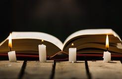 Mensonge épais de livre ouvert sur la surface en bois, bougies de cire placées dans l'arrangement avant et bel de lumière de nuit Photographie stock libre de droits