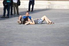 Mensonge épuisé deux par touristes au sol photos libres de droits