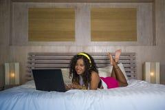 Mensonge américain de chambre à coucher de femme de jeune bel africain noir heureux à la maison gai sur le lit écoutant la musiqu photos libres de droits