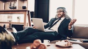 Mensonge arabe sur le divan et communiquer par le lien visuel photographie stock libre de droits