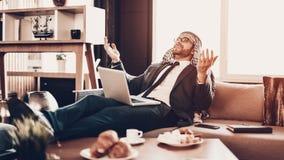 Mensonge arabe sur le divan et communiquer par le lien visuel photographie stock