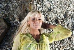 Mensonge blond sur un logarithme naturel et regarder l'appareil-photo Images libres de droits
