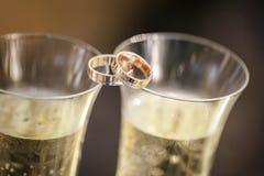 Mensonge d'anneaux de mariage sur des verres de champagne Photographie stock