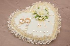 Mensonge d'anneaux de mariage sur le coussin blanc Photos libres de droits