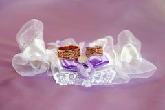 Mensonge d'anneaux de mariage sur les tissus admirablement embellis Photographie stock libre de droits