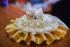 Mensonge d'anneaux de nouveaux mariés sur le grand mariage de coussin Image libre de droits