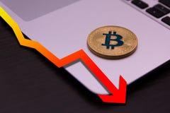 Mensonge d'or de bitcoin sur le carnet argenté avec le graphique rouge en baisse images stock