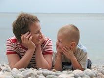 Mensonge d'enfant et de mère sur la plage Photographie stock