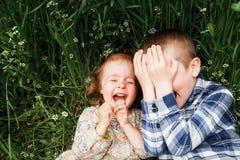 Mensonge d'enfants dans l'herbe et le rire Images libres de droits