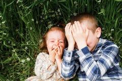 Mensonge d'enfants dans l'herbe et le rire Image stock