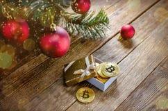 Mensonge de bitcoin de pièces de monnaie dans une boîte sous le décor de branche d'arbre de Noël Photo stock