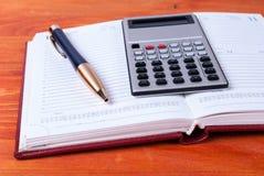 Mensonge de calculatrice et de stylo sur le journal intime ouvert Concept d'affaires photo stock