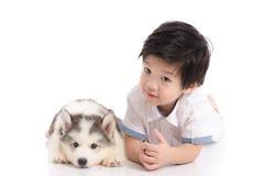 Mensonge de chiot de garçon asiatique mignon et de costaud sibérien Photos libres de droits