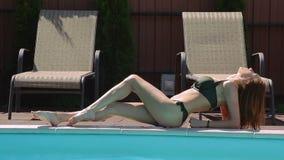 Mensonge de détente de fille de bikini au bord de la piscine clips vidéos