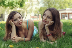 Mensonge de deux amies sur une pelouse verte Photographie stock libre de droits