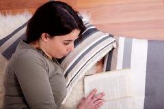Mensonge de femme, affichant un livre Photo stock