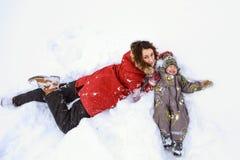 Mensonge de mère et de fils dans la neige Photographie stock libre de droits
